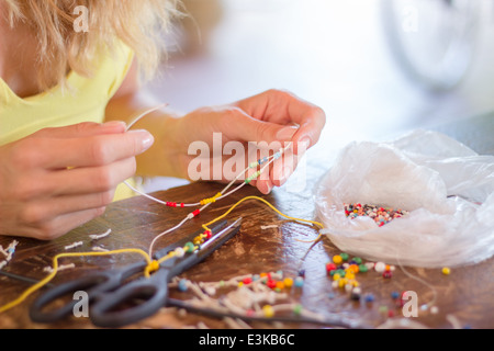 woman hands making craft crafting hobby bracelet thread threading colorful beads string craft studio - Stock Photo