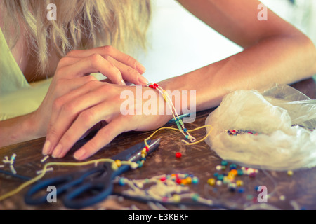woman hands making craft crafting hobby bracelet colorful beads rope - Stock Photo