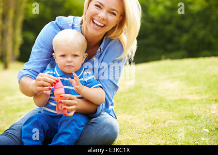 Mother Blowing Bubbles For Young Boy In Garden - Stock Photo