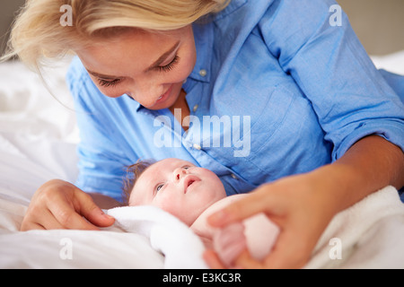 Mother Playing With Baby Girl As They Lie In Bed Together - Stock Photo