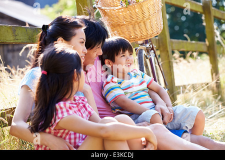 Asian Family Resting By Fence With Old Fashioned Cycle - Stock Photo