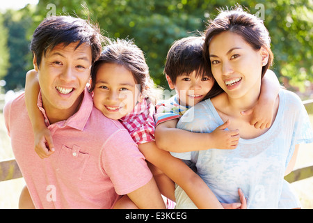 Portrait Of Asian Family Enjoying Walk In Summer Countryside - Stock Photo