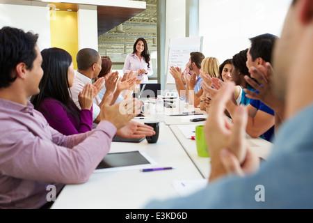Businesswoman Addressing Meeting Around Boardroom Table - Stock Photo