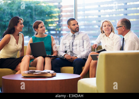 Group Of Businesspeople Having Meeting In Office Lobby - Stock Photo