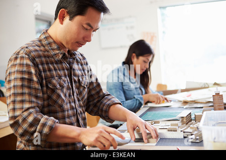 Male Architect Working On Model In Office - Stock Photo
