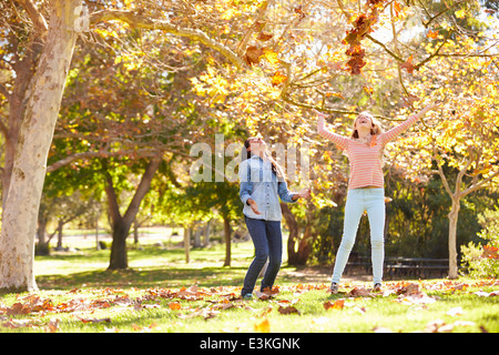Two Girls Throwing Autumn Leaves In The Air - Stock Photo