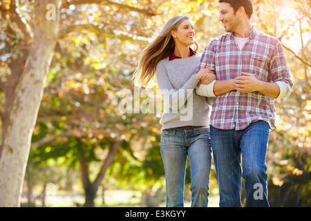 Romantic Couple Walking Through Autumn Woodland - Stock Photo