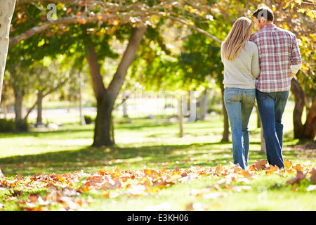 Rear View Of Romantic Couple Walking Through Autumn Woodland - Stock Photo