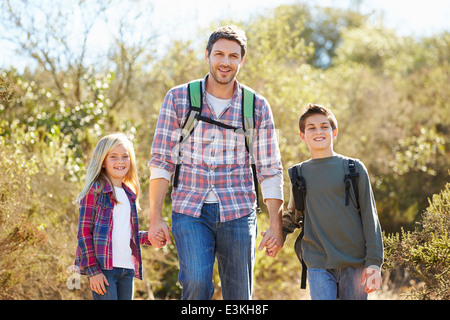 Father And Children Hiking In Countryside Wearing Backpacks - Stock Photo