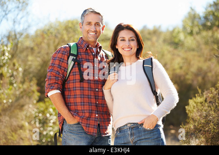 Portrait Of Couple Hiking In Countryside Wearing Backpacks - Stock Photo