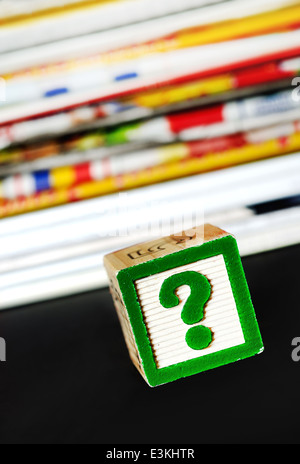 Question mark near many newspapers - Stock Photo