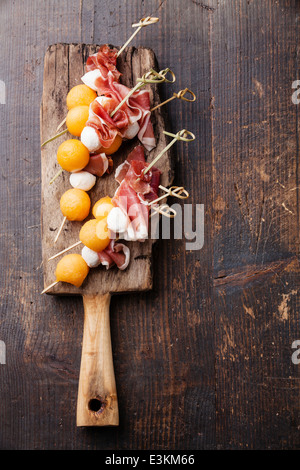 Mozzarella, prosciutto, melon canapes on textured background - Stock Photo