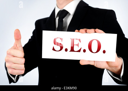 Business man showing SEO word - Stock Photo