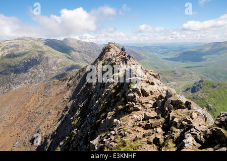 View back along red rocky Crib Goch ridge top scramble with hikers at start of Snowdon Horseshoe in mountains Snowdonia - Stock Photo