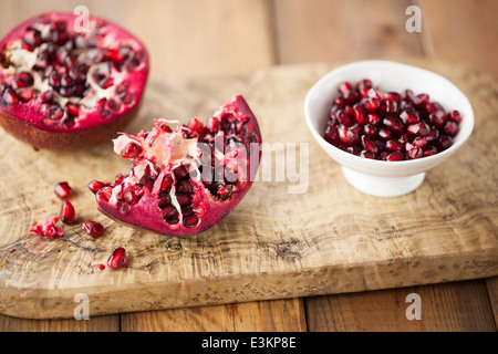 Pomegranate on Wooden Board - Stock Photo