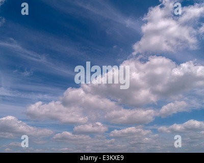 White cumulus clouds against deep blue sky with wispy high level cirrus clouds - Stock Photo