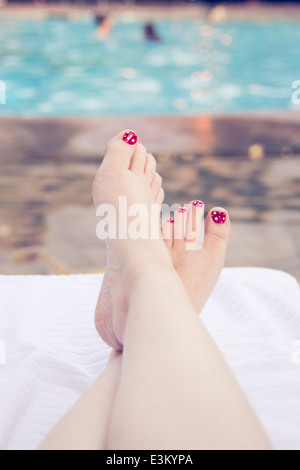 Low-section of woman relaxing near swimming pool - Stock Photo