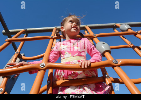 Little girl plays on a spider web in modern children toy playground in a park. - Stock Photo