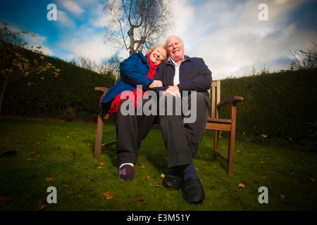 A retired couple, relaxing on a bench in a garden. - Stock Photo