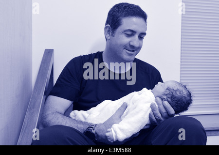 Happy father holds his newborn baby few minutes after childbirth. (BW) - Stock Photo