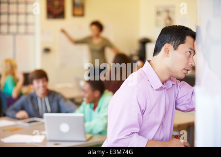 Stressed High School Teacher Trying To Control Class - Stock Photo