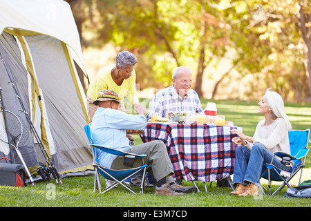 Two Senior Couples Enjoying Camping Holiday In Countryside - Stock Photo