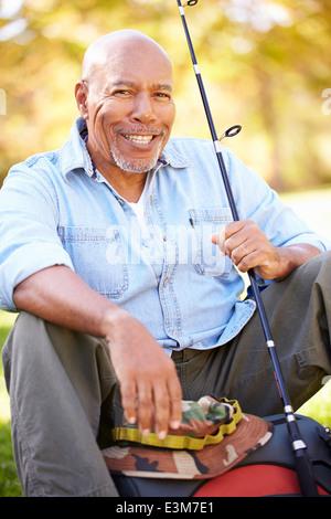 Senior Man On Camping Holiday With Fishing Rod - Stock Photo
