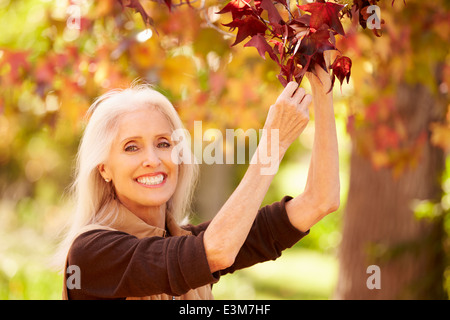 Mature Woman Relaxing In Autumn Landscape - Stock Photo