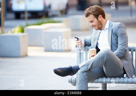 Businessman On Park Bench With Coffee Using Mobile Phone - Stock Photo