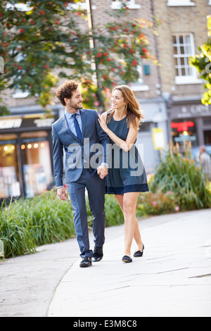 Young Business Couple Walking Through City Park Together - Stock Photo