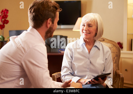 Young Man Talking To Counsellor Using Digital Tablet - Stock Photo