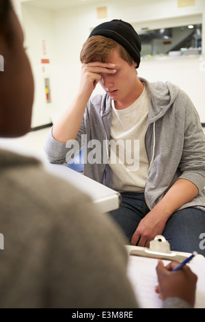Young Man Talking To Counsellor Who Takes Notes - Stock Photo