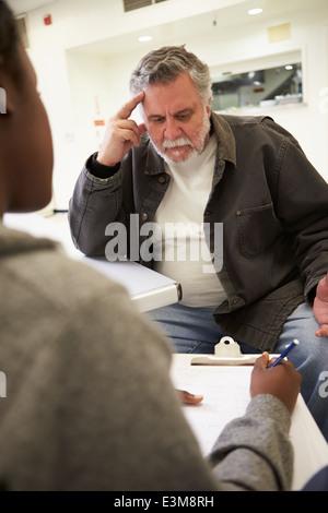 Man Talking To Counsellor Who Takes Notes - Stock Photo