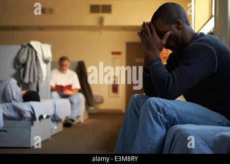 Men Sitting On Beds In Homeless Shelter - Stock Photo