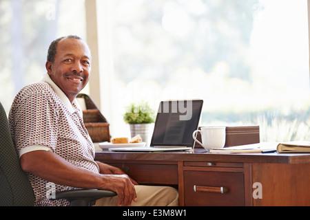 Senior Man Using Laptop On Desk At Home - Stock Photo