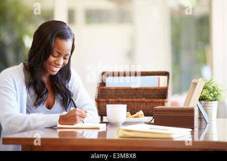 Woman Writing In Notebook Sitting At Desk - Stock Photo