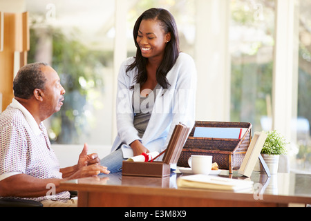 Senior Father Discussing Document With Adult Daughter - Stock Photo