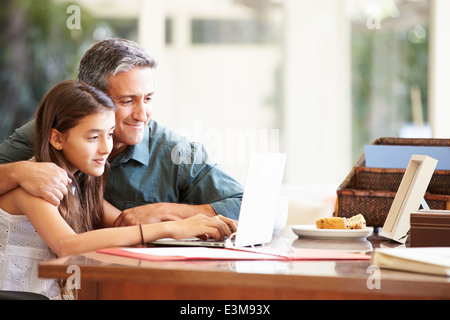 Father And Teenage Daughter Looking At Laptop Together - Stock Photo