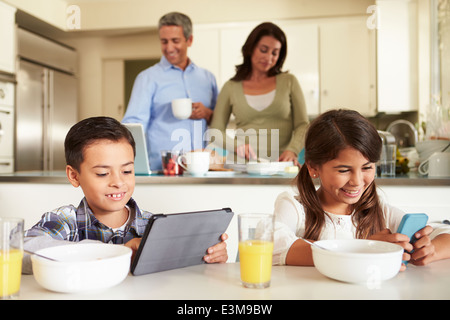 Hispanic Family Eating Breakfast Using Digital Devices - Stock Photo