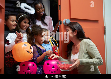 Children Going Trick Or Treating With Mother - Stock Photo