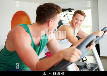 Two Young Men Training In Gym On Cycling Machines Together - Stock Photo