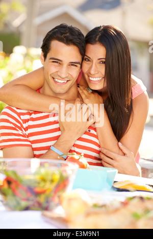 Romantic Couple Enjoying Outdoor Meal In Garden - Stock Photo