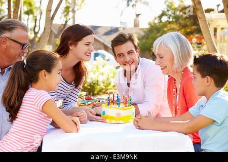 Multi-Generation Family Celebrating Birthday In Garden - Stock Photo