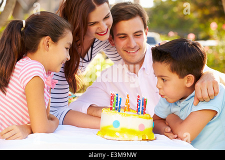 Family Celebrating Birthday Outdoors With Cake - Stock Photo