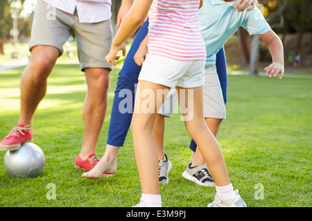 Close Up Of Family Playing Soccer In Park Together - Stock Photo