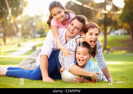 Family Lying On Grass In Park Together - Stock Photo