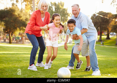 Grandparents Playing Soccer With Grandchildren In Park - Stock Photo