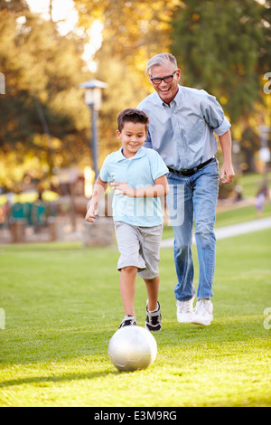 Grandfather Playing Football With Grandson In Park - Stock Photo