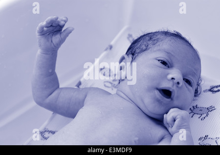 Little newborn baby (14 days old), having his first bath at home. - Stock Photo