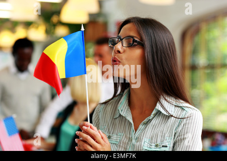 Businesswoman in glasses blowing on flag of Romania - Stock Photo
